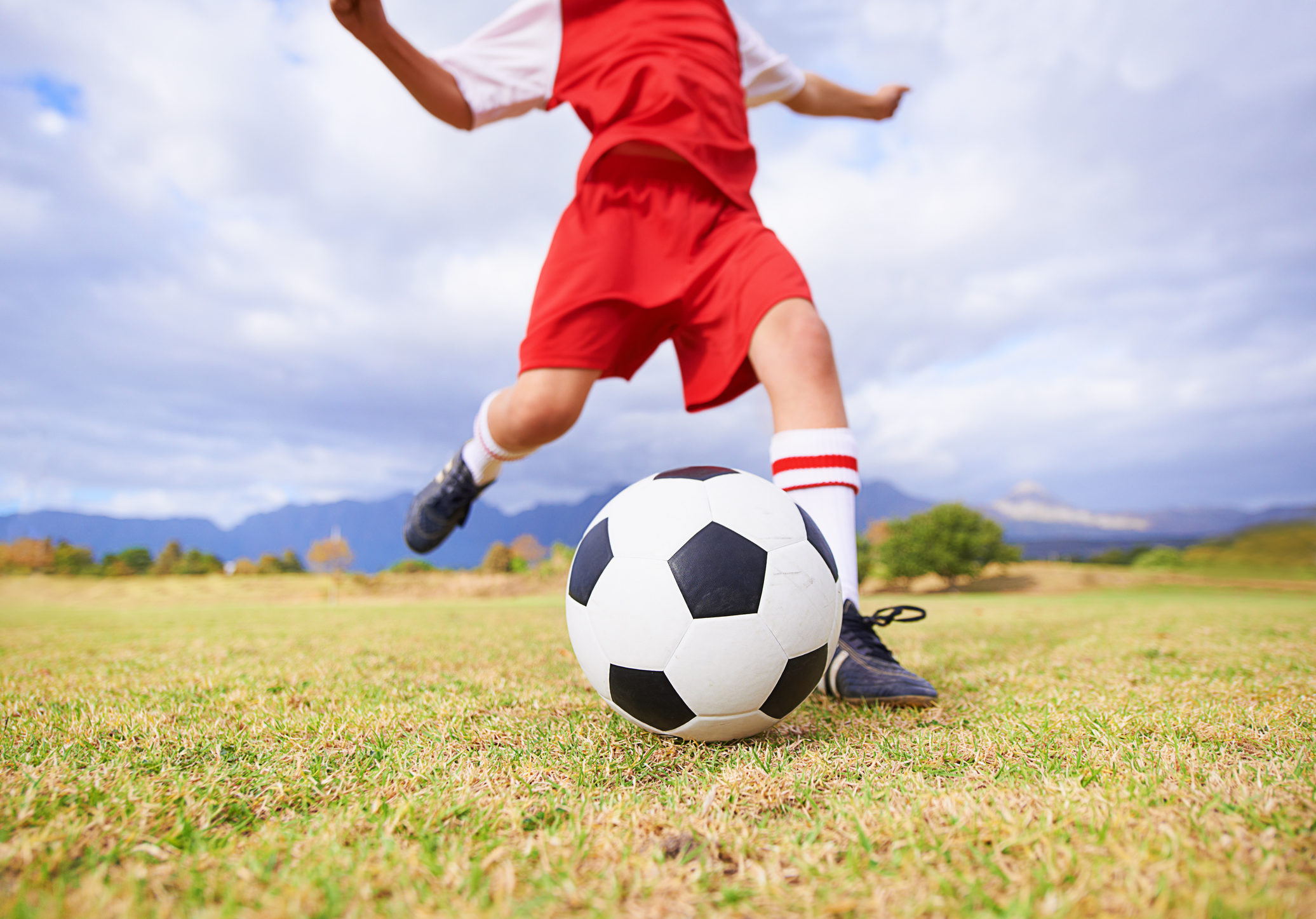 Cropped image of a child kicking a soccer ball